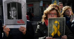 Pictures of jailed Catalan pro-independence leaders are held up during a demonstration in Barcelona, on Friday, in support of 12 pro-independence leaders that were transferred from Barcelona to Madrid ahead of the start of their trial. Photograph: Lluis Gene/AFP/Getty Images