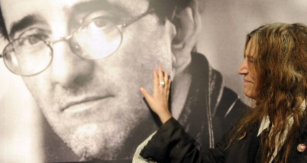 US singer Patti Smith poses in front of a giant poster of late Chilean writer Roberto Bolaño in Madrid in 2010. Photograph:  Dominique Faget/AFP/Getty Images