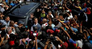 Venezuelan opposition leader and self-proclaimed interim president Juan Guaidó waves to supporters at a rally against President Nicolás Maduro's government in Caracas. Photograph: Carlos Barria