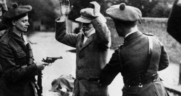 Black and Tans hold a suspected Sinn Féin member at gunpoint. A fallen man lies in the background. Photo by  Hulton-Deutsch Collection/Corbis via Getty Images