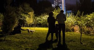 A young couple who can't afford to buy a dog for their son bring him to a Tehran park park so he can play with dogs there. Photograph: Arash Khamooshi via The New York Times