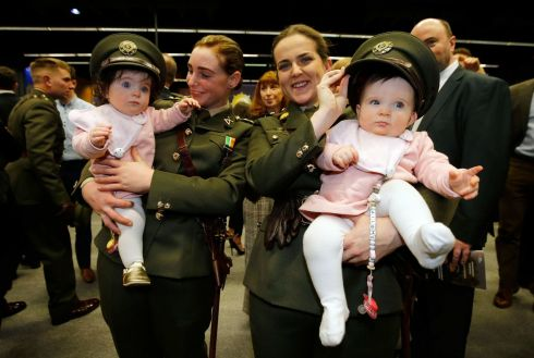 GET THEM YOUNG: Newly commissioned Defence Forces officers Kimberly King (left) holding Elsie, niece of Leanne Nolan, who is holding her twin sister, Ailbhe, at a commissioning ceremony at Dublin Castle. Photograph Nick Bradshaw/The Irish Times