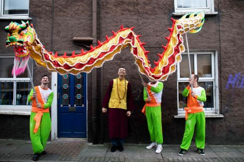 CHASING THE DRAGON: Los Angeles-based Sifu, Douglas Sutton (centre), who is the vice-abbot of Dari Rulai Temple, is accompanied by a traditional Chinese dragon carried by Martin Jacobs, Gareth Tobin and Tommy Suto, en route to Nano Nagle Place through Cork city centre while preparing for the Chinese New Year Festival celebrations. Photograph: Clare Keogh