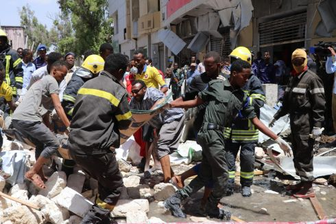 TERROR IN MOGADISHU: Rescue workers carry away a body after a car-bomb blast in the Hamarwayne District of Mogadishu, capital of Somalia. At least nine people were killed and several wounded when a car blew up near a mall in a busy market. Photograph: Abdirazak Hussein Farah/AFP/Getty Images