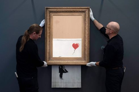 FAMED SHREDWORK: Employees hang up the artwork Love is in the Bin by British street artist Banksy at the Frieder Burda Museum in Baden-Baden, southwestern Germany. It is noted for a built-in shredder being activated as the work was being auctioned at Sotheby's in London last October. Photograph: Thomas Kienzle/AFP/Getty Images