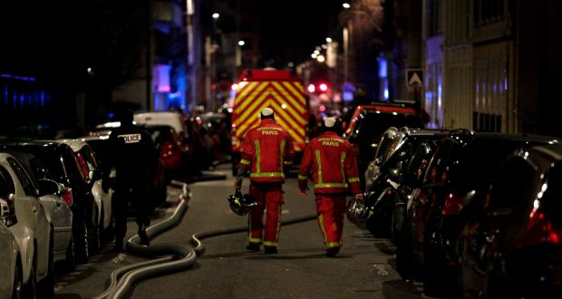 Firefighters and a police officer are seen near a building that caught fire in the 16th arrondissement in Paris. Photograph:  Geoffroy Van der Hasselt/AFP