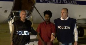 Italian police with the arrested man in 2016. Prosecutors say he is the alleged trafficker Medhanie Yehdego Mered, but he is apparently refugee Medhanie Tesfamariam Berhe. Photograph: Reuters