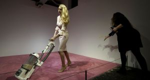 A spectator tosses crumbs for an Ivanka Trump lookalike to vacuum at Jennifer Rubell's art exhibit 'Ivanka Vacuuming' on Tuesday at Flashpoint Gallery in Washington. Photograph: Sait Serkan Gurbuz/AP
