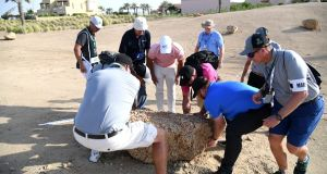Brooks Koepka is assisted in moving a loose impediment on the side of on the 15th hole during the Saudi International. Photograph: Ross Kinnaird/Getty Images