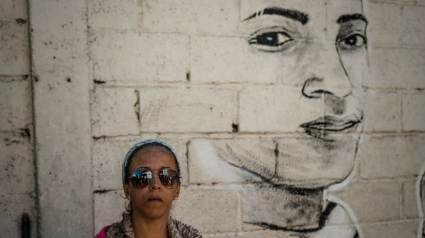 Nivea Pisani, Alixon's aunt, beside the mural paying tribute to him in Catia, Caracas. Photograph: Meridith Kohut/The New York Times