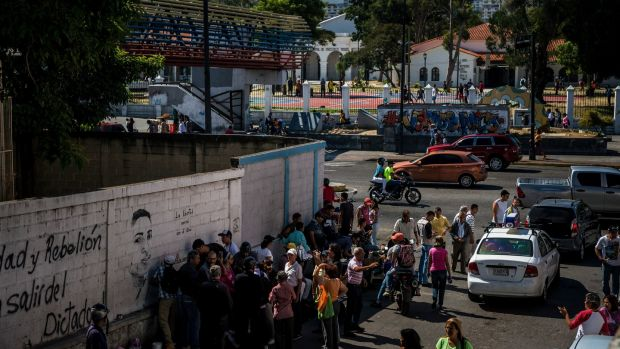 People visit a mural that pays tribute to Alixon Pisani, near where he was killed while participating in an anti-government street protest, in Catia, Caracas. Photograph: Meridith Kohut/The New York Times