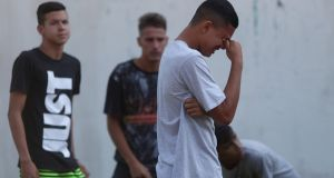 People wait for information in front of the training centre of Rio soccer club Flamengo. Photograph: Ricardo Morae/Reuters