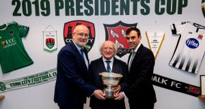 President Michael D Higgins holds the President's Cup along with FAI director of competitions Fran Gavin (left) and Cork City general manager  Paul Wycherley  at the FAI headquarters in Abbotstown in advance of Saturday's final between Cork City and Dundalk at Turner's Cross. Photograph: Stephen McCarthy/Sportsfile