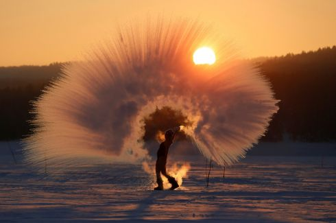 "DUBAK CHALLENGE: Winter outdoor sports enthusiast Olesya Ushakova poses at sunset outside the Siberian city of Krasnoyarsk, Russia while throwing hot water into subzero air as she participates in the ""Dubak Challenge"", a social media trend that has become popular in Russia recently. Photograph: Ilya Naymushin/Reuters"