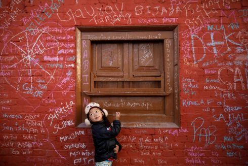 A PUPIL'S PLEA: A girl looks towards her father as she writes on the wall of a Saraswati temple in Kathmandu, Nepal, during the Shreepanchami festival dedicated to the goddess of education, Saraswati, in the belief that she will help young students. Photograph: Navesh Chitrakar/Reuters
