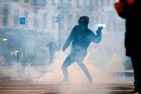 "RIGHT BACK AT YOU: A protester throws back a tear-gas canister during an anti-government demonstration called by the ""yellow vests"" (gilets jaunes) movement, in Lyon, France. One such protester reportedly lost four fingers on one hand when he touched a stun grenade in Paris on Saturday. Photograph: Alex Martin/AFP/Getty Images"