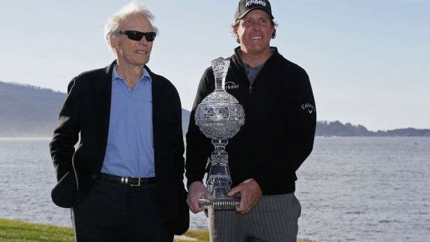 Mickelson poses with his trophy and Clint Eastwood on the 18th green. Photo: Eric Risberg/AP Photo