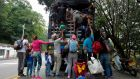 Venezuelan migrants climb on a truck on the road from Cúcuta to Pamplona in  Colombia as humanitarian aid is blocked from entering the country. Photograph: Raul Arboleda/AFP