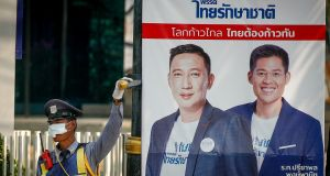A security guard stands next to an electoral poster with a portrait of Thai Raksa Chart party leader Preechapol Pongpanich (right) and a constituency candidate, in Bangkok on Wednesday. Photograph: Diego Azubel/EPA