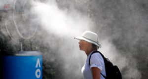 A fan stands near a fan to keep cool ahead of a match at the Australian Open tennis tournament in Melbourne. Photograph: Adnan Abidi/Reuters