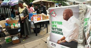 A street vendor is pictured next to a campaign poster of Atiku Abubakar, leader of the People's Democratic Party (PDP) in Lagos, February 12t. Photograph: Reuters/Luc Gnago