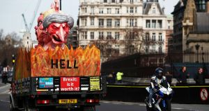 A lorry carrying an effigy of Theresa May passes outside the Houses of Parliament, in Westminster. Photograph: Hannah McKay/Reuters