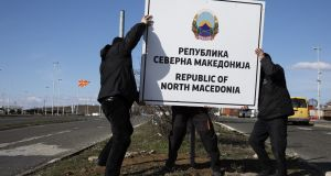 Workers erect a new road sign  at the Greece-Macedonia Bogorodica border crossing near Gevgelija on Wednesday. Photograph: Konstantinos Tsakalidis/Bloomberg