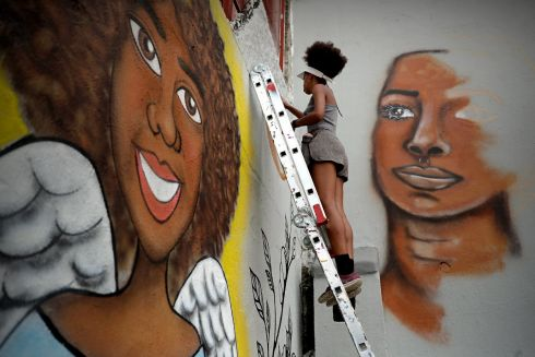 A graffiti artist and activist painting part of a 10m-high mural with the image of rights agitator Marielle Franco who was murdered 11 months ago.  Photograph: Fernando Bizerra jnr/EPA