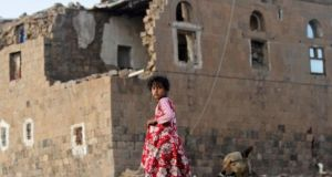 A girl walks near her house destroyed in an air strike carried out by the Saudi-led coalition in Faj Attan village, Sana'a, Yemen in December. Photograph: Mohamed al-Sayaghi/Reuters