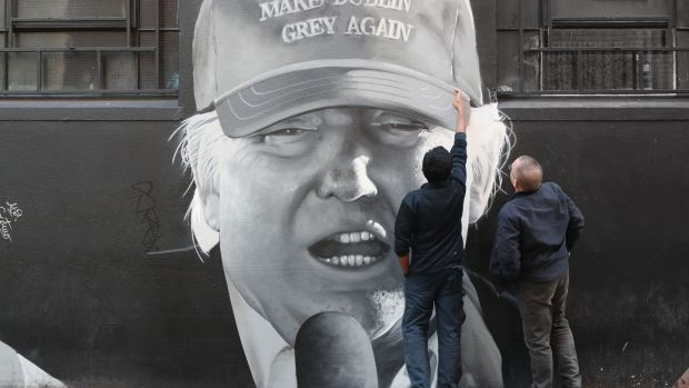 Members of the public look at a mural of US President Donald Trump in Dublin city centre by the artist group Subset. File photograph: Niall Carson/PA