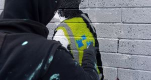 A member of the graffiti collective Subset works on a mural in Smithfield, Dublin. Photograph: Dara Mac Donaill