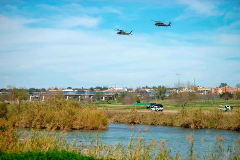 US Border Police vehicles guard as helicopters overfly the Rio Bravo. Photograph: Julio Cesar Aguilar/AFP