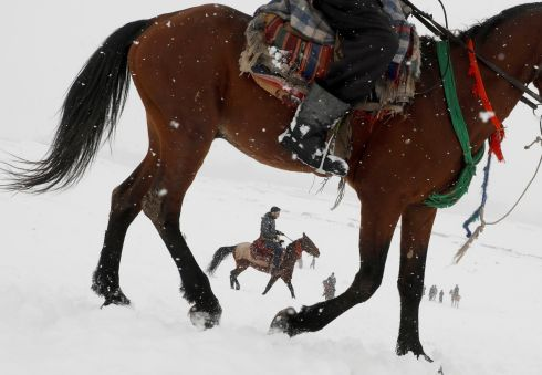 TROTTING ALONG: Afghan men ride horses on the snow-covered ground on the outskirts of Kabul, Afghanistan. Photograph: Omar Sobhani/Reuters