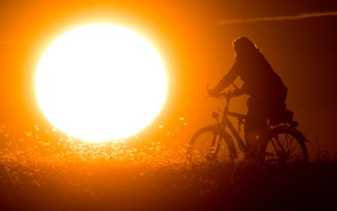 A cyclist against the morning sun in Hanover, Germany. Photograph: Julian Stratenschulte/dpa/AFP/Getty Images)