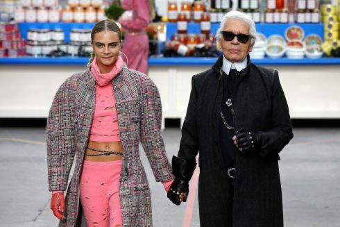"On the catwalk with model Cara Delevingne at the end of his Autumn-Winter 2014-2015 women's ready-to-wear collection show for Chanel at the Grand Palais, which was  transformed into a ""Chanel Shopping Center""  during Paris Fashion Week in March  2014. REUTERS/Benoit Tessier/File Photo"
