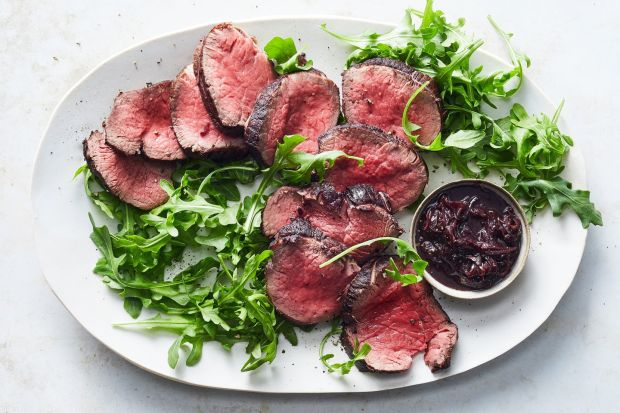 Beef tenderloin with red wine, anchovies, garlic and thyme is served with arugula in a recipe from Nigella Lawson in her iconic cookbook How To Eat. Photograph: Julia Gartland/The New York Times