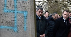 French President Emmanuel Macron visits the vandalised Jewish cemetery in Quatzenheim, eastern France, on Tuesday. French residents and public officials from across the political spectrum geared up Tuesday for nationwide rallies against anti-Semitism following a series of anti-Semitic acts, including the swastikas painted on about 80 gravestones at the Jewish cemetery. Photograph: Frederick Florin/ AP