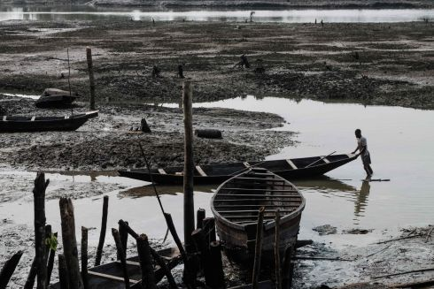 MURKY WATERS: A fisherman pushes his boat on oily mud in a river at the village of K-Dere in the Niger Delta region, after alleged oil spills in the area. Photograph: Yasuyoshi Chiba/AFP/Getty Images