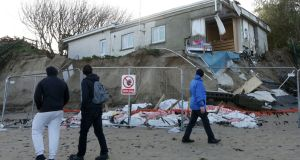 ON THE BRINK: People view the coastal erosion damage to Gráinne Hennigan's house on Portrane Beach in north Co Dublin this afternoon. The house began to collapse earlier this week. Photograph: Laura Hutton/The Irish Times
