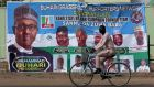 A cyclist drives pasts a campaign poster in Kano for Nigeria's president Muhammadu Buhari, on February 17th. Photograph: Luc Gnago/Reuters