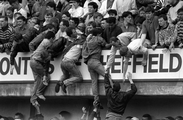 File photo dated April 15th, 1989 of Liverpool fans climbing into the upper West Stand in an attempt to escape severe overcrowding in the Leppings Lane terrace below during the FA Cup semi-final football match between Liverpool and Nottingham Forest at Hillsborough. Photograph: David Giles/PA Wire