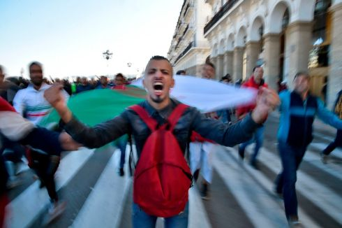 An Algerian demonstrator carries a a national flag as protests against Algeria's president's candidacy for a fifth term. Photograph: Ryad Kramdi/AFP/Getty Images