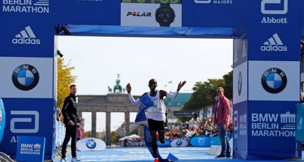 6991aec388bb Kenya s Eliud Kipchoge celebrates as he wins the Berlin Marathon and breaks  the world record in