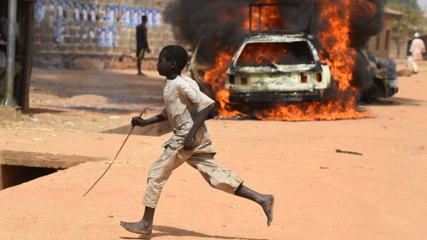 A boy runs as cars are set on fire following clashes between supporters of the ruling All Progressives Congress and the opposition People's Democratic Party at Kofa in the Bebeji district of Kano, Nigeria. Photograph: Pius Utomi Ekpei/AFP/Getty Images