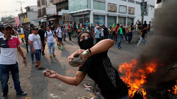 A demonstrator throws rocks during clashes with the Bolivarian National Guard in Urena, Venezuela, near the border with Colombia. Photograph: Rodrigo And/AP