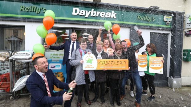Les Reilly, owner of Reilly's Daybreak Store in Naul, north Co Dublin, where the winning EuroMillions ticket was sold, celebrating with staff, customers and David Woods (left) of the National Lottery. Photograph: Mac Innes Photography