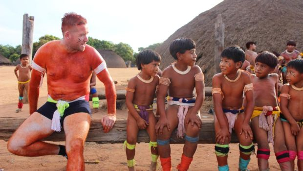 Paddy Collins and children from the Wauja tribe in the documentary series Traveller's Guide.