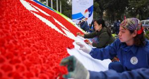 Workers make a North Korean and  US flag with paper flowers in Hanoi as US president Donald Trump gets set to meet North Korean leader Kim Jong-un. Photograph: Jewel Samad