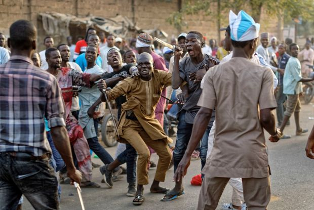 Supporters of the ruling party and main opposition party briefly pull knives and machetes on each other during an otherwise celebratory gathering of supporters of president Muhammadu Buhari anticipating victory, in Kano, northern Nigeria on Monday. Photograph: Ben Curtis/AP
