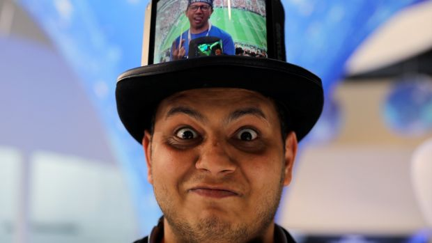 A visitor poses while wearing a hat packed with a Flexible+ display by the Chinese company Royole. Photograph: Reuters